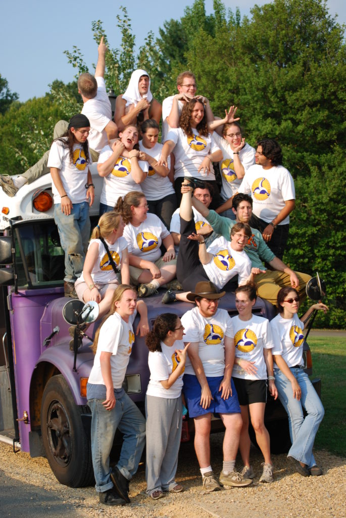 Traveling Players staff goofing off on top of a purple bus