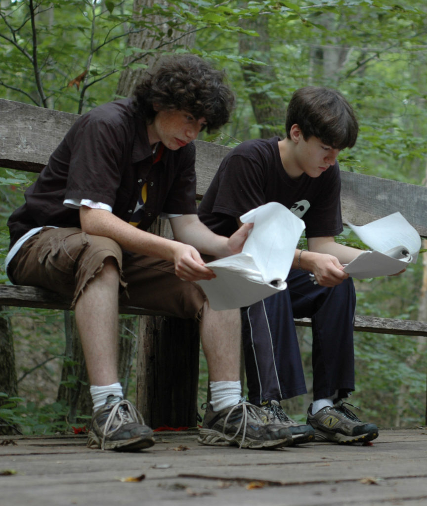 two campers reading their scripts
